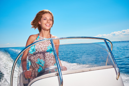 Summer vacation - young woman driving a motor boat