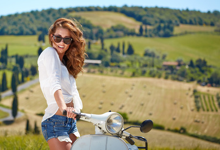 cuntry: Young beautiful italian woman sitting on a italian scooter in Italy hills