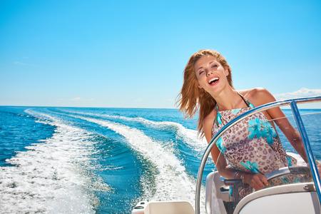 conduciendo: Vacaciones de verano - mujer joven que conduce un barco de motor Foto de archivo