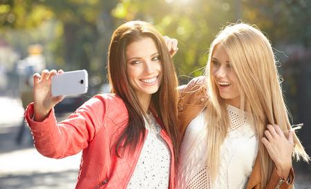 Amigos fazendo selfie. Duas belas mulheres jovens fazendo selfie Imagens