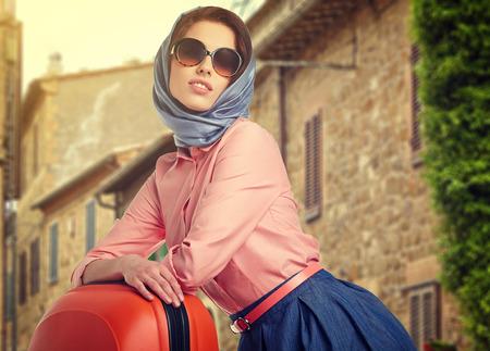 mujer elegante: Mujer elegante con un recorrido de la maleta en la calle de la ciudad italiana Foto de archivo