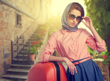 Elegant woman with a suitcase travel on street of italian city photo