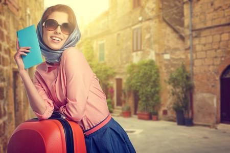 viaggi: Donna elegante con un viaggio valigia e biglietto sulla via della città italiana
