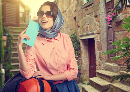 Elegant woman with a suitcase travel and ticket on street of italian city photo