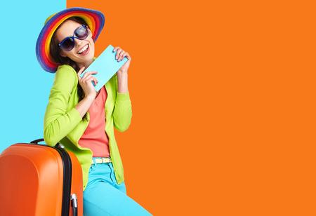 Turysta kobieta z walizką podróży i niebieskie karty pokładowej, odizolowane na lato tła