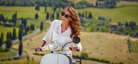 vespa: Joven y bella mujer italiana sentado en una moto italiana en Italia colinas