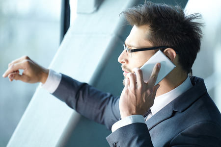 businessman waiting call: Businessman talking on mobile phone in office lobby