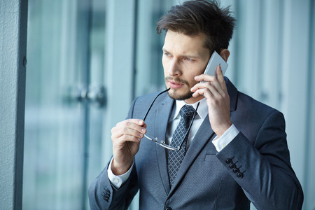 business communication: Businessman talking on mobile phone in office lobby