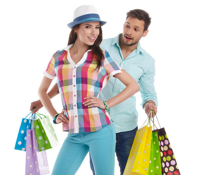 Attractive young couple with shopping bags on white background photo