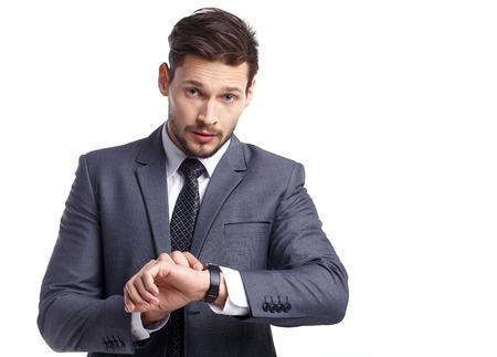 hombres guapos: joven hombre de negocios que mira el reloj sobre el fondo blanco