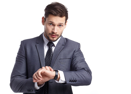 checking: young business man  looking at watch over white background Stock Photo