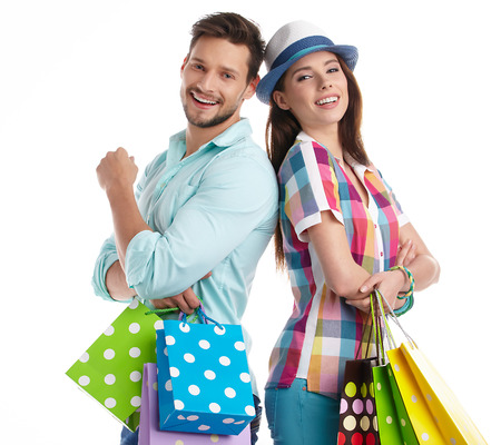 attractive lady: Attractive young couple holding shopping bags on white background