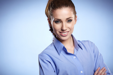 young executives: Portrait of a beautiful young business woman standing against blue background Stock Photo