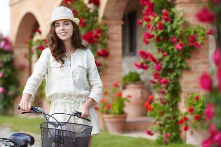 agriturismo: Woman with bike in Tuscany rose garden