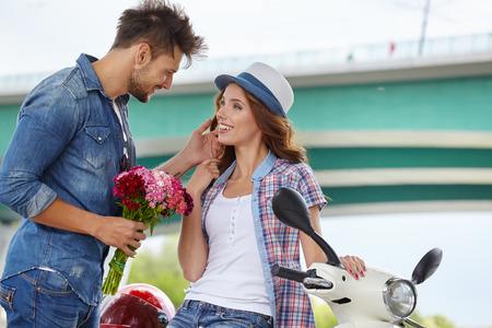 Portret van romantische man bloemen geven aan vrouw