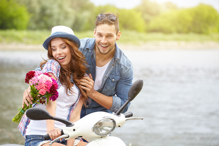 Ein Mann gibt schöne Frau Blumen. Im Hintergrund der Fluss und Roller Lizenzfreie Bilder