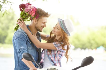 ロマンス: 男が花を与える美しい女性。背景川とスクーターで 写真素材