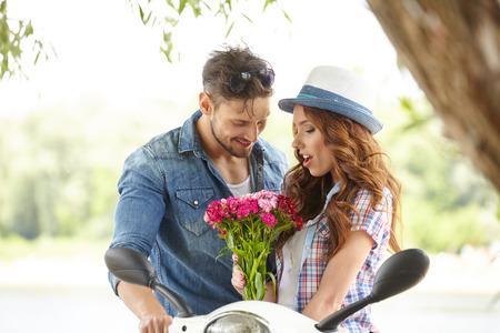 sorpresa: Un hombre da flores hermosa mujer. En el fondo del río y scooters