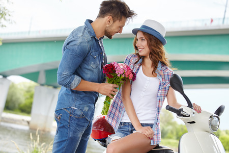 romantic man: Portrait of romantic man giving flowers to woman Stock Photo