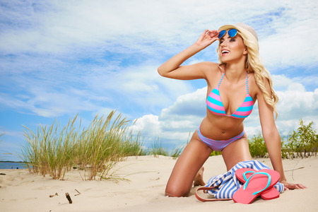 sun down: Beach woman funky happy and colorful wearing sunglasses and beach hat having summer fun during travel holidays vacation. Stock Photo