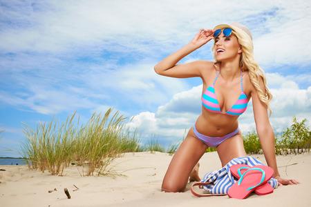 gafas de sol: Mujer de la playa con gafas de sol cobardes felices y coloridas y sombrero de playa que se divierte el verano durante las vacaciones de viaje de vacaciones. Foto de archivo