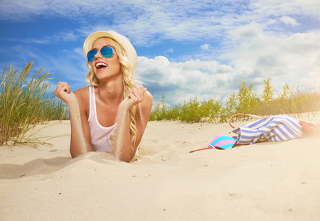Beach woman funky happy and colorful wearing sunglasses and beach hat having summer fun during travel holidays vacation. Stock Photo