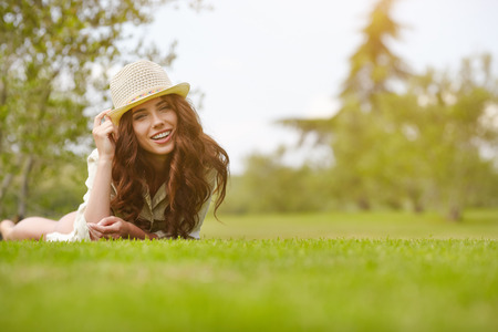 lying on grass: Beautiful Young Woman Outdoors. Enjoy Nature. Healthy Smiling Girl in Green Grass. Stock Photo