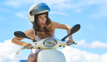 Young beautifulsexy woman sitting on a scooter outdoor Stock Photo