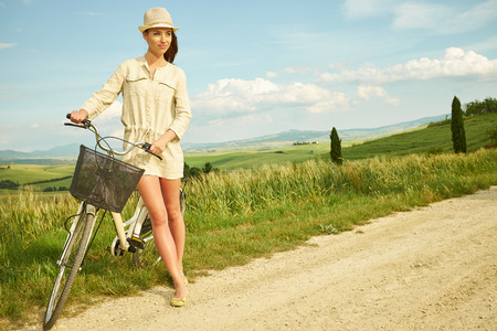woman in field: beautiful vintage girl sitting next to bike, summer time