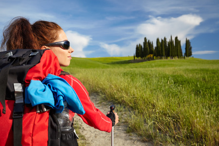 Female hiking woman happy and smiling during hike trek on Toscana hills Stock Photo