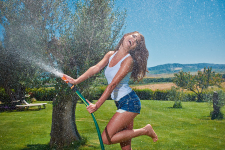 Beautiful young woman having fun in summer garden with garden hose splashing summer rain.