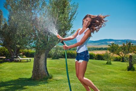 Mujer joven hermosa que se divierte en el jardín de verano con la manguera del jardín lluvia salpicar verano.