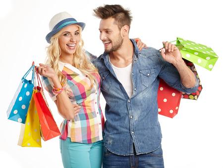 Pareja joven y atractiva con bolsas de la compra en el fondo blanco Foto de archivo - 42185553