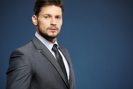 man business: Handsome young business man standing on blue background