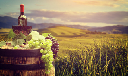 glass bottles: Red wine bottle and wine glass on wodden barrel. Beautiful Tuscany background