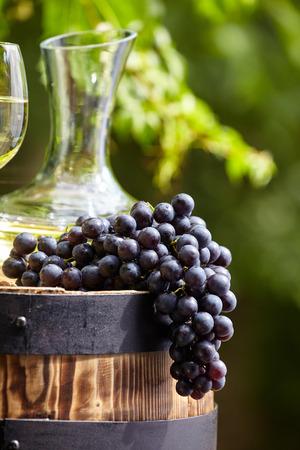wine grape: Grape and white wine on wooden barrel on garden terrace