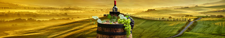 vine country: Red wine bottle and wine glass on wodden barrel. Beautiful Tuscany background