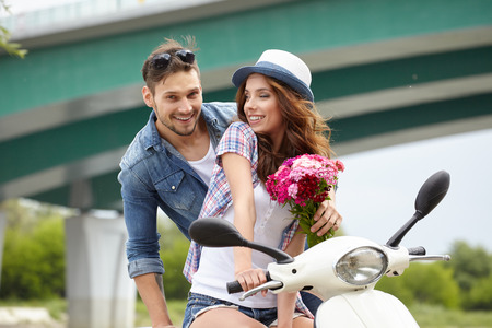 gives: A man gives flowers to beautiful woman on scooter