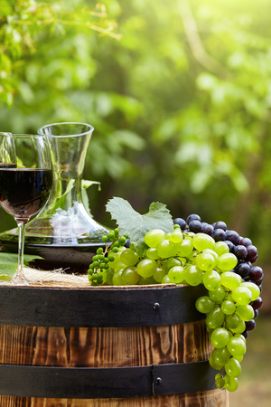 wine glass: Old wooden barrel with glass of red wine.