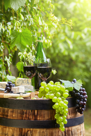 vine country: Old wooden barrel with bottle and glass of red wine.