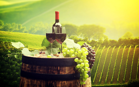 grapes wine: Red wine bottle and wine glass on wooden barrel, Beautiful Tuscany background