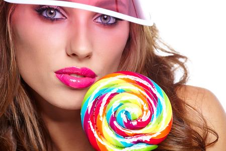 pink lips: Glamourous girl wearing plastic cap holding lollipop