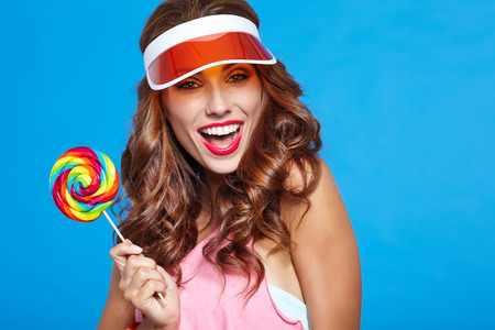 beautiful background: Beauty summer model girl Eating colourful lollipop on blue background