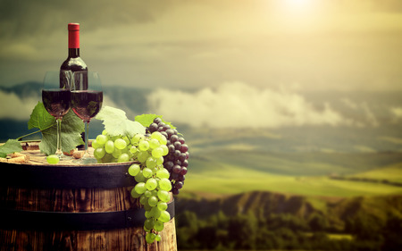 wine grape: Red wine bottle and wine glass on wodden barrel. Beautiful Tuscany background