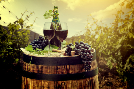 wine country: Red wine bottle and wine glass on wodden barrel. Beautiful Tuscany background