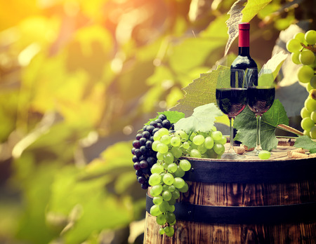 Red wine bottle and wine glass on wodden barrel. Stock Photo - 44900121