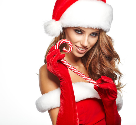 christmas woman: Beautiful woman with santa hat holding red-white Christmas Lollipop