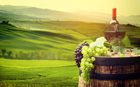 glass of red wine: Red wine bottle and wine glass on wooden barrel, Beautiful Tuscany background