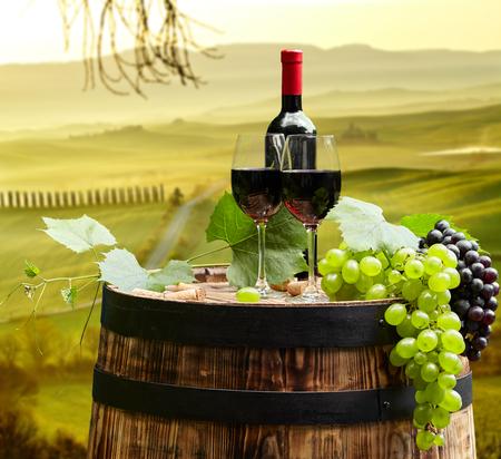 uvas: Botella de vino tinto y copa de vino en el barril de madera, hermoso fondo Toscana