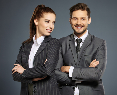 young couple smiling: Business couple on grey background